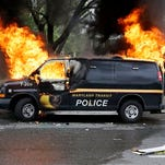 A police vehicle burns, Monday during unrest following the funeral of Freddie Gray in Baltimore. Gray died from spinal injuries about a week after he was arrested and transported in a Baltimore Police Department van.