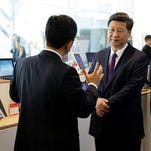 Harry Shum, left, Microsoft Executive Vice President of Technology and Research, talks with Chinese President Xi Jinping, right, in front of a display of devices running the Windows operating system that were made in China by ZTE Corporation during a tour of Microsoft's main campus in Redmond, Wash., Wednesday.