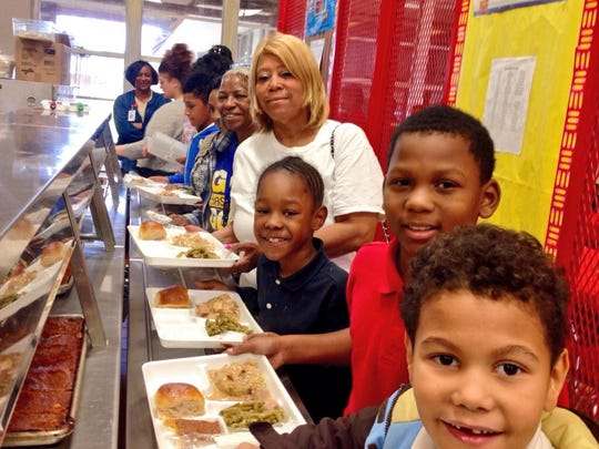 Ruth Ann Williams gets Christmas lunch Wednesday at Acadian Elementary with grandsons (from back left to front) Taylor White, Jayvain Knox and Braylean White.