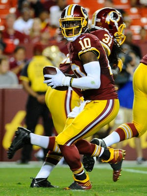 Washington Redskins quarterback Robert Griffin III (10) rolls out against the Detroit Lions during the first half at FedEx Field.
