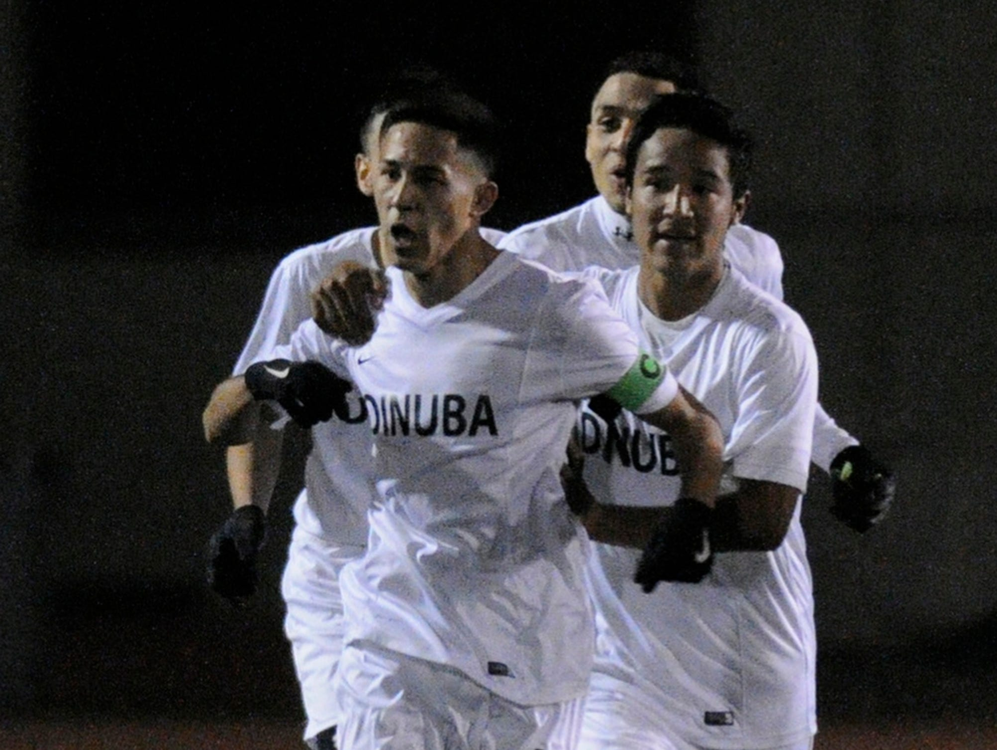 Dinuba's Chris Amaro celebrates with teammates after scoring a goal in the Central Section Division III championship.