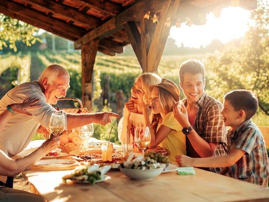 Portait of a big family having a picnic at a vineyard