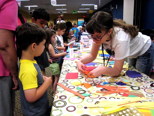 Teen volunteer Julia Spano assists SCLSNJ branch staff