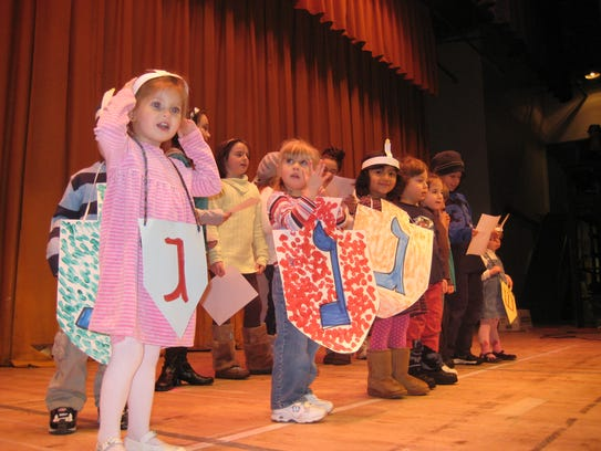 Children act out songs during a celebration marking