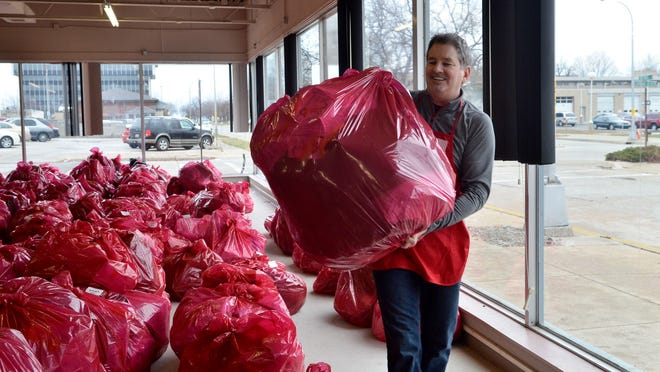 Jim Charron carries a large bag of toys and gifts to a family Thursday during the Salvation Army Christmas giveaway at the former Art Van building in downtown Port Huron.