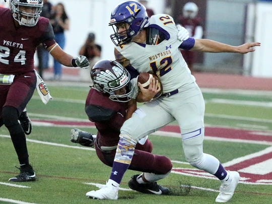 Burges wide receiver Christian Yeager, 12, is brought down by Ivan Urquidi of Ysleta Friday night at Ysleta.