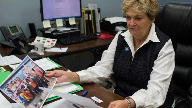 Rae Logan, executive director of 232-HELP, sorts through images of various programs organized by the organization in Lafayette, La., Wednesday, Sept. 9, 2015.