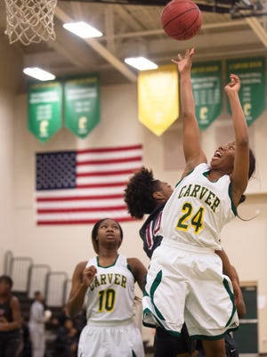 Carver Adasia Rudolph (24) shoots a layup over Stanhope Elmore's Natalia Whitted (14) during the basketball game on Friday, Feb. 12, 2016, in Montgomery, Ala.
