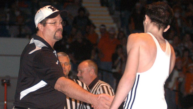 Ryle head coach Tim Ruschell congratulates his son, T.J. Ruschell, after he won his first Kentucky state championship match at 110 pounds at the Frankfort Convention Center in 2011. T.J. is now wrestling at Wisconsin.