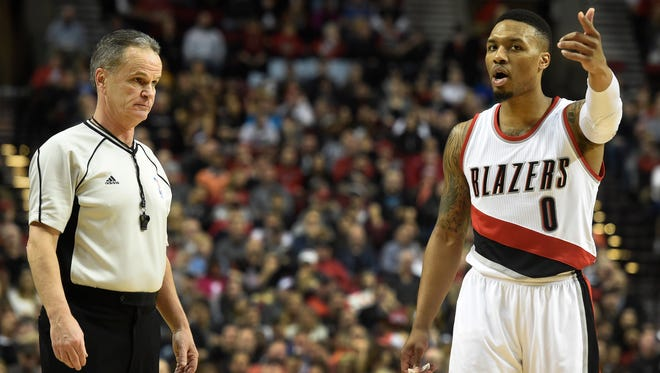 Portland Trail Blazers guard Damian Lillard (0) argues a cal with referee Mike Callahan (24) during the first half of an NBA basketball game in Portland, Ore., Tuesday, Feb. 23, 2016.