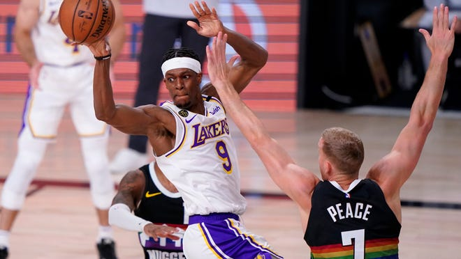 Los Angeles Lakers guard Rajon Rondo (9) makes a pass under pressure from Denver Nuggets' Mason Plumlee, right, during the first half of Game 3 of the NBA basketball Western Conference final Tuesday, Sept. 22, 2020, in Lake Buena Vista, Fla.