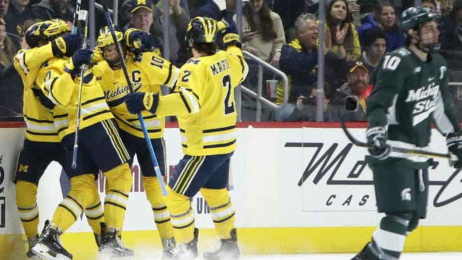 Michigan State forward Sam Saliba, right, skates away while Michigan forward Will Lockwood (10) celebrates his goal with teammates during the first period of a game Monday, Feb. 17, in Detroit.
