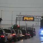 Traffic stops as the Causeway Bridge over Lake Pontchartrain is closed due to severe weather, Monday, April 27, 2015, in Metairie, La. A line of severe thunderstorms continues moving across southeast Louisiana, bringing high winds and power outages and covering some roads with water. (AP Photo/Butch Dill)
