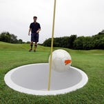 """In a photo from June 20, 2014 in Salem Township, Mich., Josh Maxam, left, watches as Brian Eggenberger drives during a round of FootGolf at Fox Hills Golf Course. FootGolf, a soccer-golf hybrid is helping courses draw younger, more diverse customers. Players """"tee off"""" _ minus the tees of course _ by kicking a soccer ball from the tee box. They follow the basic rules of golf from there, advancing the ball until it drops into the oversized hole. (AP Photo/Carlos Osorio)"""