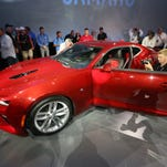Journalists and fans surround the new 2016 Chevrolet Camaro after it was unveiled during a news conference on Belle Isle Park in Detroit