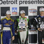 Marco Andretti, left, Carlos Munoz of Colombia, center, and Simon Pagenaud of France hold their winners trophies after the first race of the IndyCar Detroit Grand Prix auto racing doubleheader Saturday, May 30, 2015, in Detroit. Munoz won his first IndyCar race in the rain shortened event. (AP Photo/Carlos Osorio)