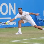 Serbia's Viktor Troicki plays a return to Croatia's Marin Cilic during their singles tennis match at the Queen's Championships in London, Thursday.