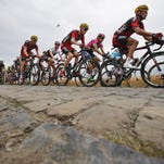 Tejay van Garderen of the U.S., center in red and black jersey, follows teammate Manuel Quinziato of Italy as the pack passes over the first cobblestone sector near Pont-a-Celles during the fourth stage of the Tour de France cycling race over 223.5 kilometers (138.9 miles) with start in Seraing, Belgium, and finish in Cambrai, France on Tuesday.