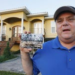 In this July 23 photo, Efrem Garza stands before his new home built on the lot of his previous house that was destroyed by Hurricane Katrina and holds a photograph taken by a friend of the remains of that house on South Seashore Avenue in Long Beach, Miss. Before the storm Garza was surrounded by houses and trees, now 10 years later, there are only two houses on that land, as few of the residents returned and rebuilt.
