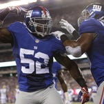 New York Giants middle linebacker Jon Beason (52) celebrate with teammate Devon Kennard (59) after breaking up a pass to Jacksonville Jaguars' Denard Robinson during the first half of a preseason NFL football game Saturday, Aug. 22, 2015, in East Rutherford, N.J.