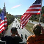 Residents wave American flags from the Turk Hill Road bridge as the Traveling Vietnam Veterans Memorial Wall travels along Interstate 684 in the town of Southeast Sept. 23, 2015. The wall was traveling to the Putnam County Veterans Memorial Park in Carmel where it will be on display From Sept. 24th to the 27th.