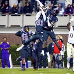 Knights' wide receiver Breshad Perriman, 11, catches the game winning touchdown pass against East Carolina Pirates linebacker Dayon Pratt, 1, and defensive back Domonique Lennon ,31, during the fourth quarter at Dowdy-Ficklen Stadium. UCF defeated the East Carolina Pirates 32-30.