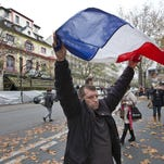 A man displays the French flag on Tuesday in front of the Bataclan concert hall, which was a site of last Friday's attacks, in Paris. France is demanding security aid and assistance from the European Union in the wake of the Paris attacks and has triggered a never-before-used article in the EU's treaties to secure it.