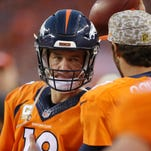 Denver Broncos quarterback Peyton Manning (18) looks at quarterback Brock Osweiler (17) on the sidelines after being benched during the second half against the Kansas City Chiefs at Sports Authority Field at Mile High.