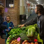 Tamara Allison buys vegetables from Sprout Urban Farms' mobile market after school at Riverside Elementary with her children Jacob Allison and Abbygail Mitchell.