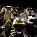 FSU players hold up a gator head in celebration after beating Florida 27-2 at Ben Hill Griffin Stadium in Gainesville on Saturday.