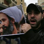 A Bahraini protester holds a picture of Saudi Shiite cleric Sheikh Nimr al-Nimr during a rally denouncing the execution of Shiite cleric Sheikh Nimr al-Nimr by Saudi Arabia, Sunday, Jan. 3, 2016, in Daih, Bahrain. Saudi Arabia announced the execution of al-Nimr on Saturday along with 46 others. Al-Nimr was a central figure in protests by Saudi Arabia's Shiite minority until his arrest in 2012, and his execution drew condemnation from Shiites across the region. (AP Photo/Hasan Jamali)