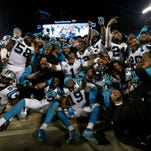 The Carolina Panthers celebrate on the sideline in the fourth quarter against the Arizona Cardinals during the NFC Championship Game at Bank of America Stadium on January 24, 2016 in Charlotte, North Carolina.
