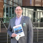 David Ziegler, national sales manager of the Cincinnati USA Convention & Visitors Bureau, photographed Friday, Jan. 29, 2015 with promotional pieces produced for the Lions bid.