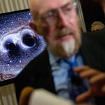 A visual of gravitational waves from two converging black holes is depicted on a monitor behind Laser Interferometer Gravitational-Wave Observatory (LIGO) Co-Founder Kip Thorne as he speaks to members of the media following a news conference at the National Press Club in Washington, Thursday, Feb. 11, 2016, as it is announced that scientists they have finally detected gravitational waves, the ripples in the fabric of space-time that Einstein predicted a century ago. The announcement has electrified the world of astronomy, and some have likened the breakthrough to the moment Galileo took up a telescope to look at the planets. (AP Photo/Andrew Harnik)