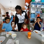 Child-care provider Tonja Boggs starts to clean up as Tayshariah White, 6 (from left), Josiah Coleman, 1, and Gregory White, 7, finish up their afternoon snacks Feb. 11, 2016, at her home in Des Moines.
