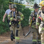 Tallahassee firefighters leave the scene of a Byington Place house fire where a Leon County teacher Rajames Scott and her two young daughters Anisha and Aniyah died Friday morning.