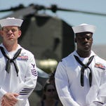 Navy enlisted personnel stand in front of a helicopter during the Memorial Day remembrance ceremony at the Northern Nevada Veterans Memorial Cemetery.
