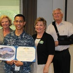 Christopher Porquaido holds the Navy and Marine Corps Achievement Medal he was presented by Pensacola State College President Ed Meadows. Also pictured are Pensacola State Board of Trustee Chairwoman Margie Moore, far left, and Linda Whitenton, Warrington campus dean.