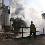 An Iranian oil worker walks at Tehran's oil refinery south of the capital in Iran. As world powers edge toward a possible nuclear deal with Iran, the debate has been dominated by the question whether it leaves an opening for Iran to acquire a nuclear weapon.