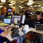 In this photo from Aug. 14, 2014, support team members work at their stations at Hudl, in Lincoln, Neb. Hudl is a software company that has developed a way to immediately get game film to coaches after games and break down and separate different plays by type.