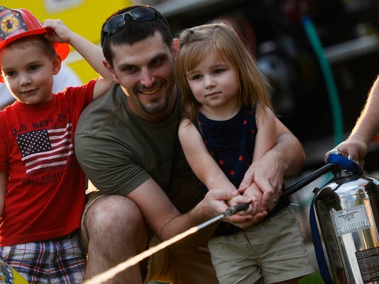 Eric Davidson of Shiloh guides his daughter, Mackenzie Davidson, 2, as she sprays down fire cutouts as Max Davidson, 4, watches at the Olde Tyme Carnival in West Manchester Township Tuesday, July 21, 2015. The West Manchester Township Fire Department was also giving rides in their bucket truck. Kate Penn   Daily Record/Sunday News