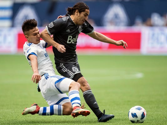Montreal Impact's Ken Krolicki, left, slides to tackle Vancouver Whitecaps' Efrain Juarez during the first half of an MLS soccer game in Vancouver, British Columbia, Sunday, March 4, 2018. (Darryl Dyck/The Canadian Press via AP)
