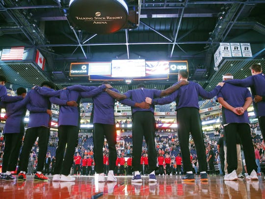 Phoenix Suns players put their arms around each other during the National Anthem before playing against the Portland Trail Blazers in pre-season NBA action at Talking Stick Resort Arena in Phoenix, Ariz. October 11, 2017.