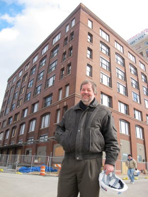 Dean Amhaus, president of the Water Council, stands outside a former factory building as it was being renovated to house the Global Water Center in Milwaukee.