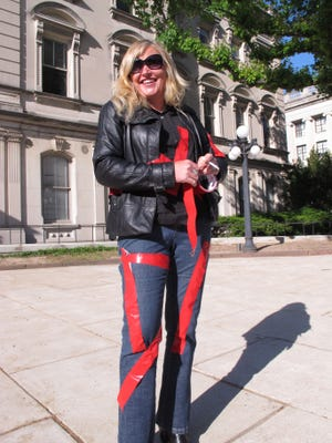 Wendy Joan, of Brick, N.J., wrapped herself in red tape before a protest rally by victims of Superstorm Sandy outside the New Jersey Statehouse in Trenton N.J. on Thursday May 14, 2015. She said the tape symbolizes the many impediments to recovery that many storm victims must overcome in getting government aid to repair their homes. (AP Photo/Wayne Parry)