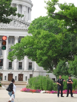 Police officers direct people away from the Capitol during a bomb threat that led to evacuation of the building and grounds while the state Assembly was debating the budget Wednesday, July 8, 2015, in Madison, Wis. The state Department of Administration said the building was clear of any threat, but that no further details would be released Wednesday because an investigation is ongoing.