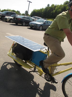 Off in a flash: Josh Traeger, who works with Brattleboro-based nonprofit VBike, scoots through the National Life Group parking lot in Montpelier in 2015 astride an electric-assist cargo bicycle.