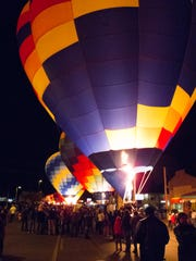 Hot air balloons glow in the night sky on Lake Powell Boulevard in Page as their pilots participate in the 13th annual Page Lake Powell Hot Air Balloon Regatta Saturday, Nov. 8, 2015. A weekend filled with fantastic ballooning weather saw 60 hot air balloons filling the skies over Lake Powell on Friday, Saturday and Sunday mornings.