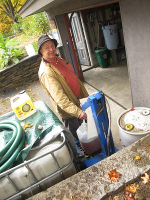 Tom Miller of Brattleboro pumps out his 5-gallon collection jug at Rich Earth Institute. His donation will be added to a larger batch, at left, to fertilize nearby hayfields.
