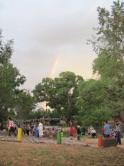 Crowds gather for a dawn flag ceremony Saturday beneath a rainbow at Colorado City's Cottonwood Park. Residents and numerous out-of-town visitors held the community's Fourth of July celebration ahead of the holiday to make it easier for visitors to attend.